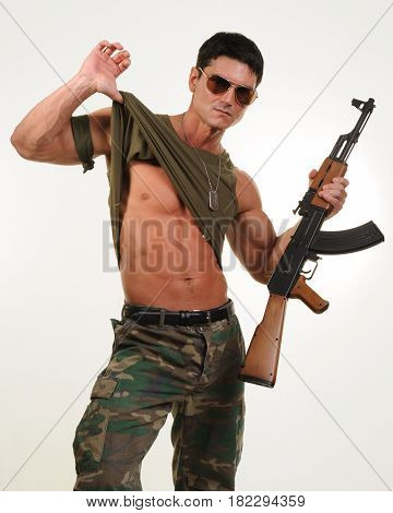The rough and rugged military man holds a gun.
