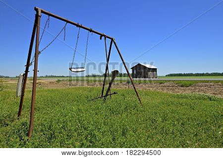 An old worn out swing set in a rural area with a shed in the background.