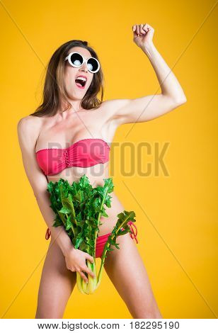 Portrait of young healthy woman in white bikini and white sunglasses play funny with fresh chicory in hand. Funny Vegetables Concept. Isolated on yellow.