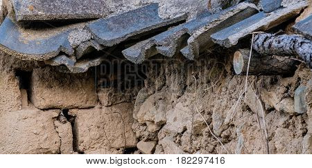 Closeup of a mud brick wall with black tile roof fallen into state of disrepair in South Korea