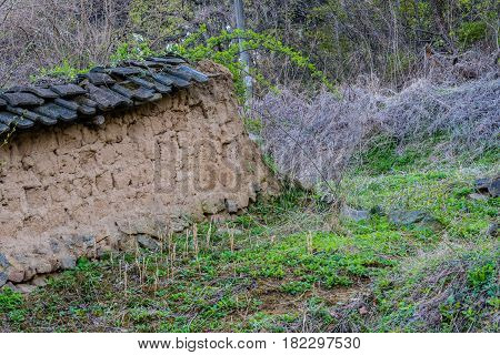Mud brick wall with black tile roof fallen into state of disrepair in wooded area South Korea