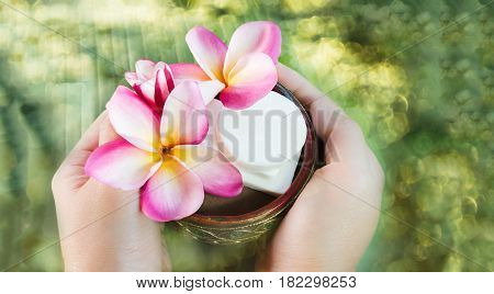 Hand take mini set of bath soap with flowers frangipani on water bokeh abstract background