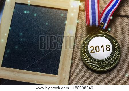 Number 2018 On Coin Or Medal Prize With Blank Copy Space Backround Small Green Board In Lense Flare