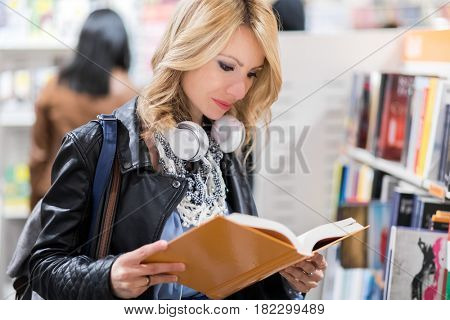 Woman reading a book in a bookstore