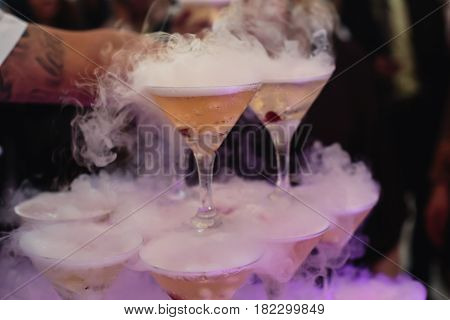 Beautiful row line of different colored alcohol cocktails with mint on a christmas party, martini, vodka,and others on decorated catering bouquet table on open air event, picture with beautiful bokeh