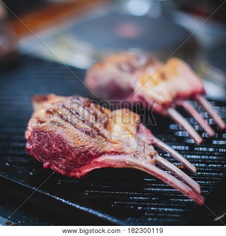 Different stages of cooking the steak on a kitchen, barbeque, roasted lamb ribs, big dish plate with roasted full pork head, served in restaurant with vegetables, lamb, ham and chicken.