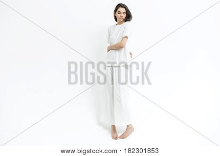 Gorgeous barefoot girl is posing in the studio on the white background. She wears a white T-shirt and pants. Woman holds her hands around the waist and looks downward. Horizontal.
