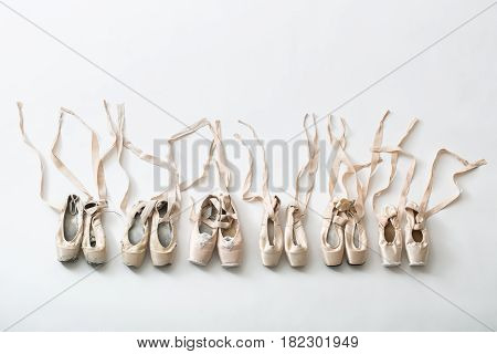Many pairs of ballet shoes in pairs stand in a row. Pointe shoes in different condition from new to very shabby old. Tapes are accurately laid out in different directions. Studio shooting, horizontal top shot.