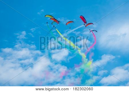 The multicolored powered parachutes in the clear blue sky.