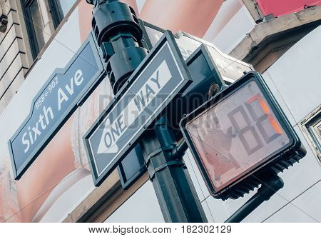 Street sign of Six Ave with skylines in background.- New York USA