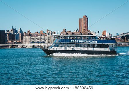 New York City USA - March 19 2017: Tourist boats on East River in front of Manhattan A East River ferry boat travels the Hudson River