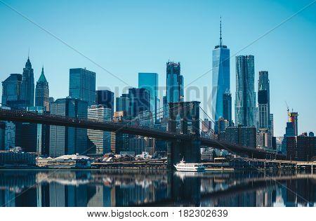 View of Brooklyn Bridge and Manhattan skyline WTC Freedom Tower from Dumbo Brooklyn. Brooklyn Bridge is one of the oldest suspension bridges.