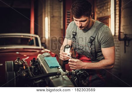 Mechanic working on classic car engine in restoration workshop