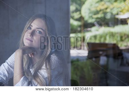 Young serious woman sitting in cafe photographed through window glass from outside with copy space