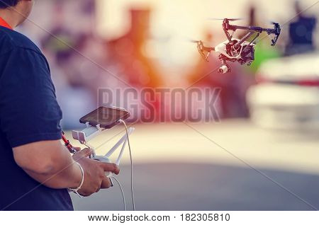 Man controling a drone flying in the sunlight