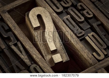 question mark - vintage wooden letterpress type block in old typesetter drawer among other letters, sepia toned black and white image
