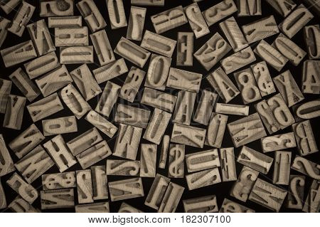 background of randomly placed wooden letterpress printing blocks, sepia toned black and white image