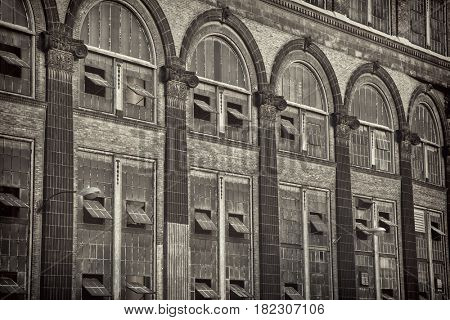 old power plant - windows and brick walls with sandstone decoration, sepia toned black and white image