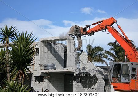 Demolition in progress of unfinished concrete houses.