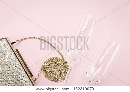 Festive Evening Golden Clutch And Two Champagne Glasses On Pink. Holiday And Celebration Background.