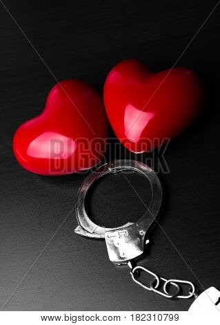 Two red hearts and steel handcuffs on dark background.St Valentine day and Fifty shade of black concept