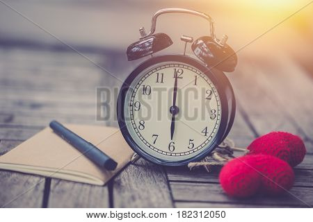 retro clock time at 6 o'clock with notebook or memo on wood table times of love memory writing diary concept vintage color tone.