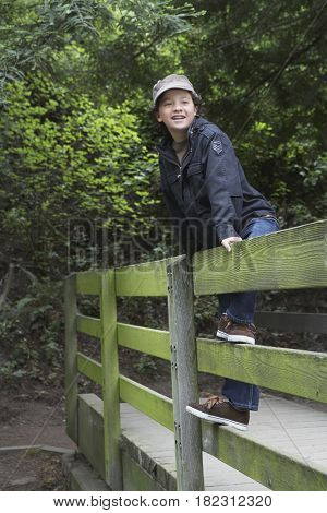 Mixed race boy climbing on wooden fence