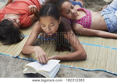 Asian girl laying and reading with friends