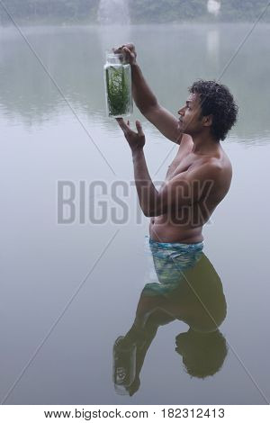 Mixed race man wading in lake with insect jar