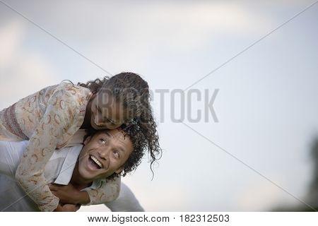 Mixed race man giving girlfriend piggy back ride