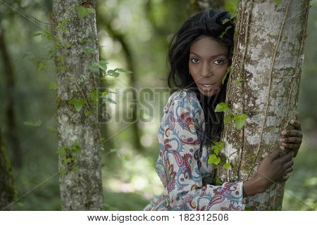 African woman hugging tree trunk