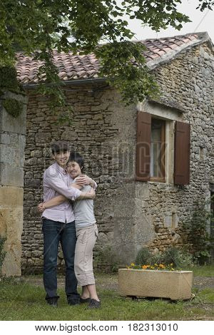 Asian couple hugging outdoors near house