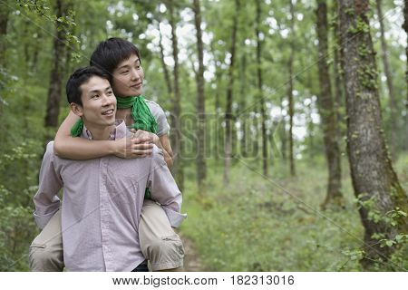 Asian man giving girlfriend piggy back ride in forest