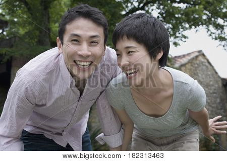 Asian couple bending and laughing