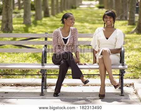 Women in trendy fashions sitting in park