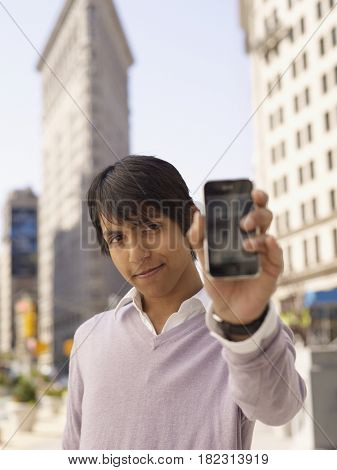 Indian man holding out cell phone