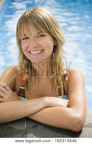 Smiling Hispanic woman standing in swimming pool