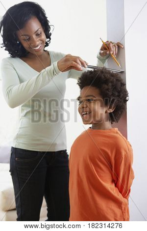 African mother measuring son's height