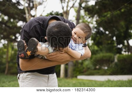 Asian father tickling son in park