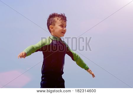 Young surfer with bodyboard having fun, sunny blue sky background