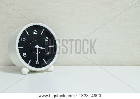 Closeup black and white alarm clock for decorate show show half past three o'clock or 3:30 p.m. on white wood desk and cream wallpaper textured background with copy space