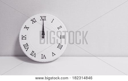 Closeup white clock for decorate in 12 o'clock on white wood desk and wallpaper textured background in black and white tone with copy space