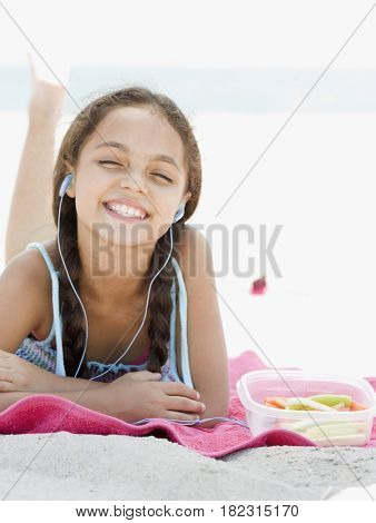 Hispanic girl listening to mp3 player on beach