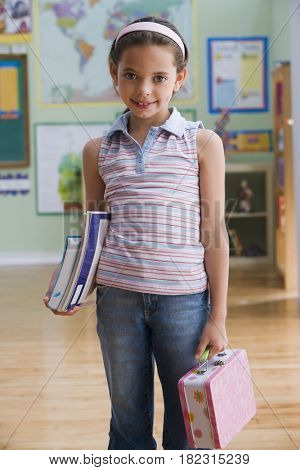 Hispanic girl holding schoolbooks and lunch box in classroom