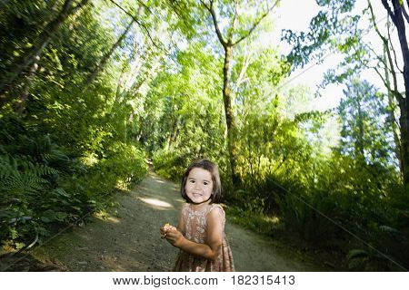 Chinese girl walking along remote wooded path