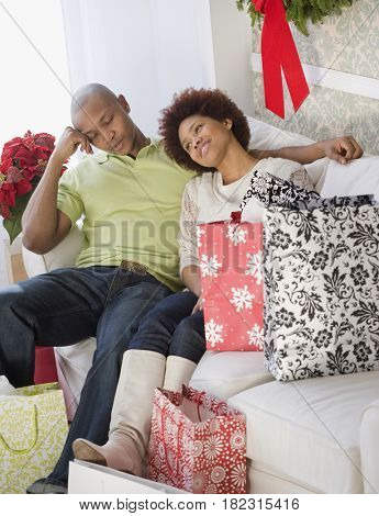 Tired African man sitting on sofa with girlfriend and shopping bags