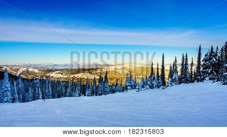 Beautiful scenery of a sunny blue sky over the majestic mountains of the Shuswap Highlands from Sun Peaks, British Columbia, Canada