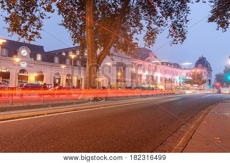 Toulouse, France - October 27, 2017; Evening city image with glow of lights on street path and buildings with Matabiau Railway Station in background Toulouse France.