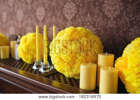 Yellow candles and a ball out of paper laying on wooden shelves, a vintage style of house decoration.