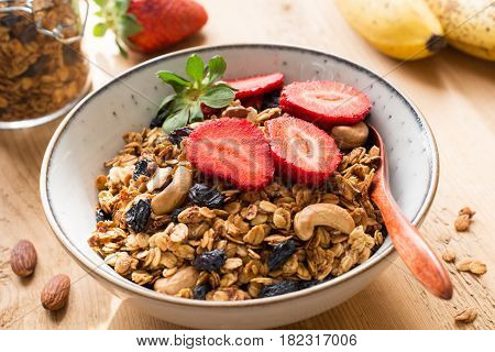 Granola with fresh strawberries, dry fruits and nuts in bowl. Healthy breakfast granola, homemade banana granola